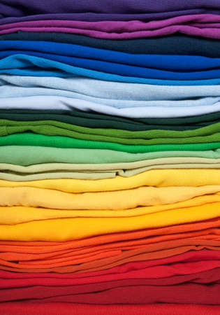 Rainbow clothes background. Pile of bright folded clothes. photo
