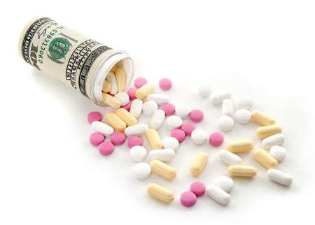 recetas medicas: P�ldoras coloridas derraman de una botella de dinero, sobre fondo blanco.