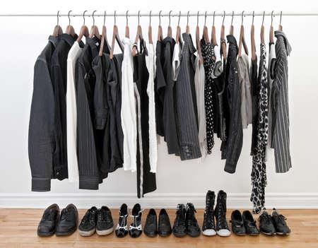 Vrouwelijke en mannelijke zwarte en witte kleren op een staaf en schoenen op een houten vloer.
