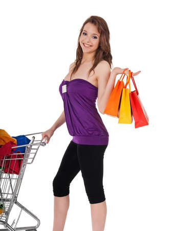 Pretty girl with bags and shopping cart full of colorful clothing, isolated on white. photo