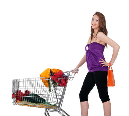 Young girl with shopping cart buying colorful clothes, isolated on white. photo