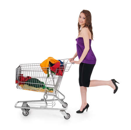 Smiling girl with shopping cart buying colorful clothes, isolated on white.