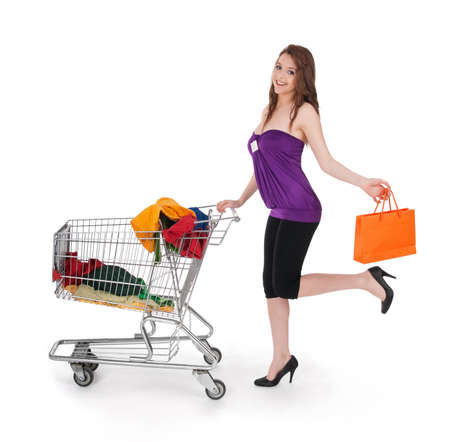 woman shopping cart: Smiling girl with shopping cart and orange gift bag, isolated on white.