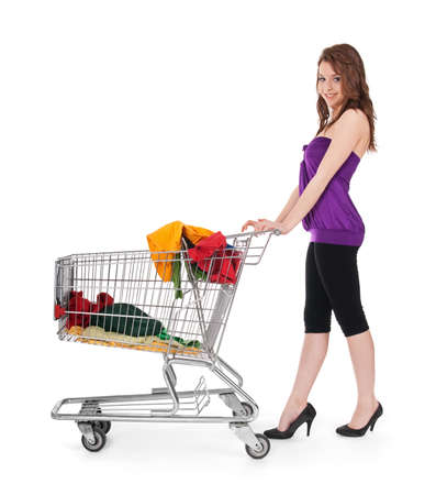 Pretty girl with shopping cart buying colorful clothing, isolated on white. Stock Photo