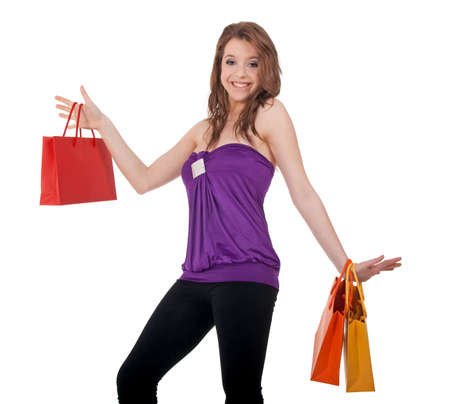 Funny young girl with colorful shopping bags, isolated on white. photo