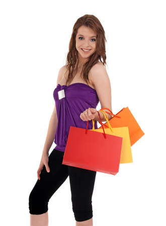 Smiling young girl holding colorful shopping bags, isolated on white. photo