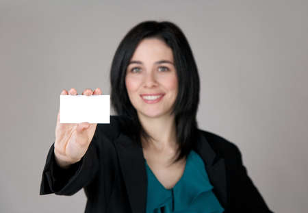 Smiling woman showing a business card with copy space. Focus on the card. photo