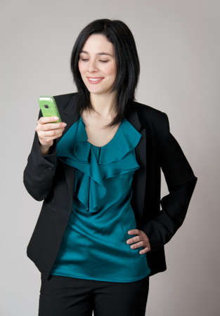 Business woman looking at her cell phone and smiling. photo