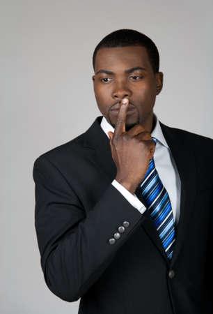 hombre pensando: Aparece un hombre de negocios estadounidense pensando y celebrar un dedo sobre sus labios.