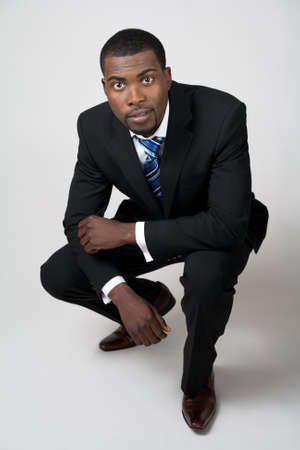 squatting: African American business in black suit squatting. Stock Photo