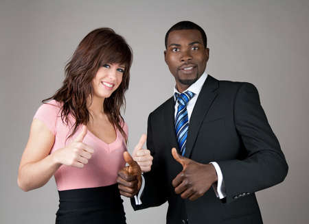 thumbs up: Male and female business partners going thumbs up.
