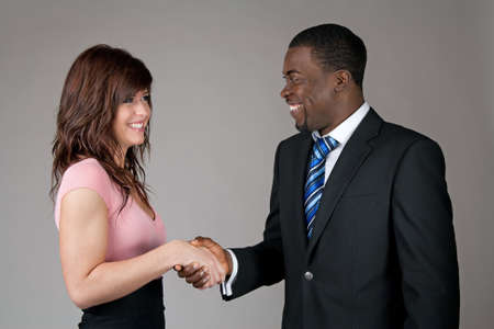 african business: Smiling young woman and African American business man shaking hands. Stock Photo