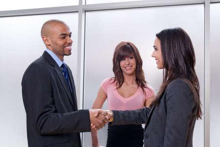 Business team of three, man and woman shaking hands. photo