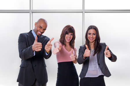 Happy multiracial business team going thumbs up. photo