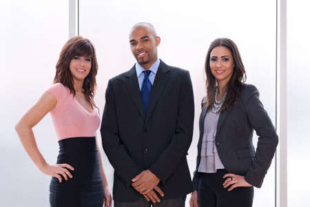 Gelukkig en trots commercieel team, drie glimlachende jonge mensen.