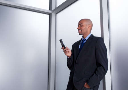 Young businessman beside an office window looking at his cell phone, smiling. photo