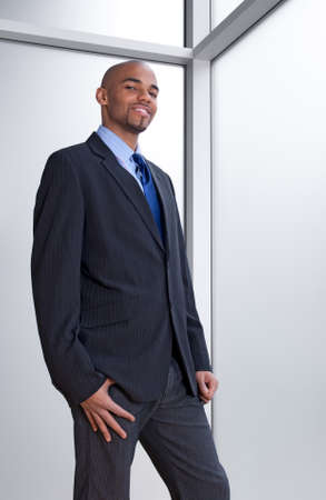 Smiling young business man beside an office window. Stock Photo - 9609402