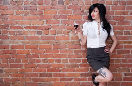 Black-haired tattooed girl with a glass of red wine leaning against a brick wall. 免版税图像