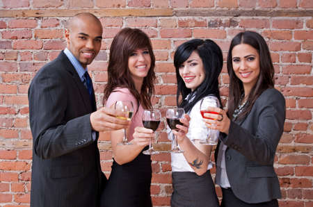 Cheers! Smiling young people with glasses of wine, having fun. Stock Photo