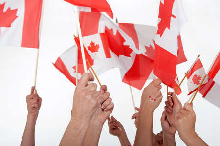 canada: Happy Canada Day! Raised hands waving Canadian flags. Stock Photo