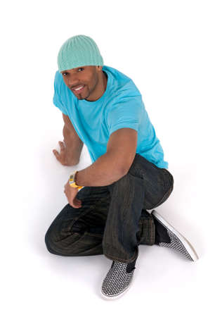 Relaxed young man in a blue t-shirt sitting on the floor, smiling. Isolated on white.