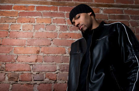 Tough guy dressed in black near a brick wall. Stock Photo - 9710787