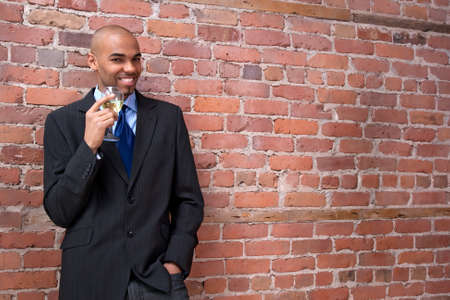 dressed for success: Young business man leaning against the brick wall, drinking wine and smiling.