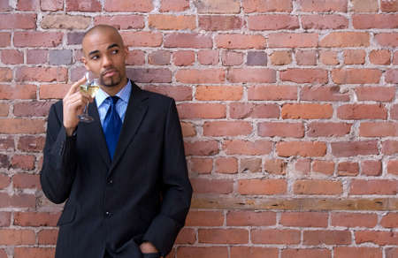 Young business man leaning against the brick wall, thinking and drinking wine. photo