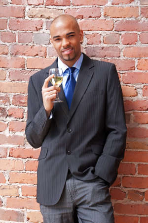 Young business man with a glass of white wine near a brick wall. Stock Photo - 9710791