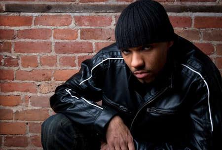 rapper: Guy aspecto peligroso vestida de negro, sentado cerca de una pared de ladrillos.