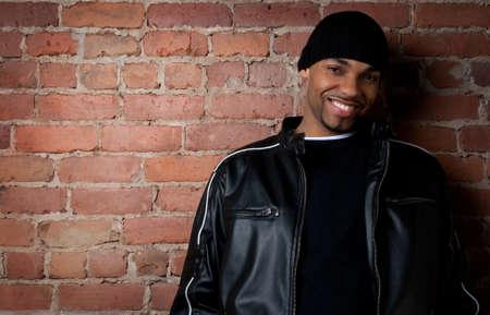 estilo urbano: Guy sonriente vestida de negro cerca de una pared de ladrillos. Foto de archivo
