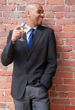 Laughing young business man with a glass of white wine, near a brick wall. Banco de Imagens