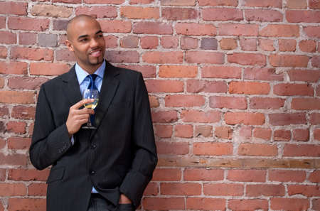 Smiling young business man leaning against the brick wall, smiling and drinking wine.