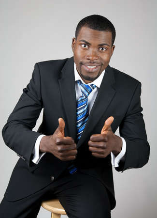Smiling successful African American businessman with thumbs up. photo