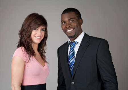 Young smiling business partners, Caucasian woman and African American man.