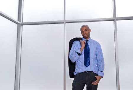Good-looking relaxed businessman standing beside a big office window. Stock Photo - 10119373