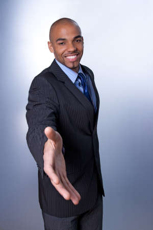 mulatto: Good-looking young businessman giving hand and smiling. Stock Photo