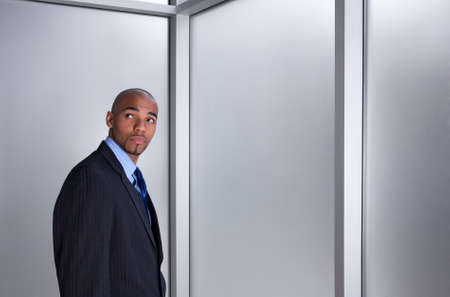 Young businessman looking anxious and worried, standing beside a window. photo