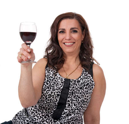 age forty: Smiling mature woman with a glass of red wine, isolated on white background.