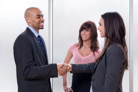 mani che si stringono: Business team di tre, uomo e donna, stringe la mano e sorridente.