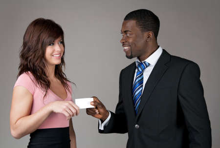 African American businessman giving his business card to a young Caucasian woman. photo