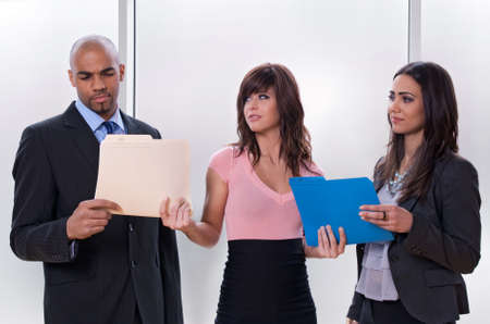 Young woman giving tasks to her colleagues who look skeptical. photo