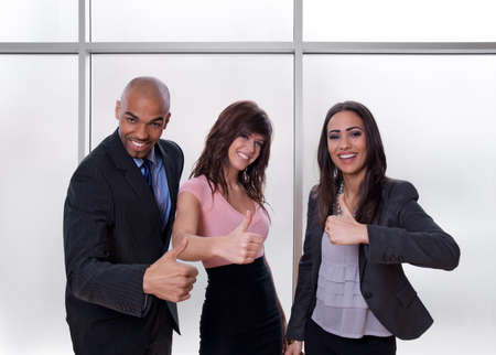 encourage: Young multiethnic business team smiling and showing thumbs up. Stock Photo