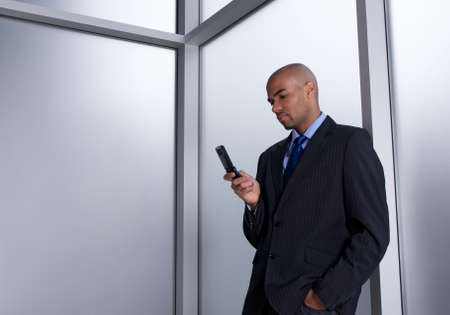 Businessman beside an office window, sending a message with his cell phone. Stock Photo - 10763846