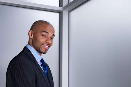 Portrait of a smiling good-looking businessman beside an office window. photo