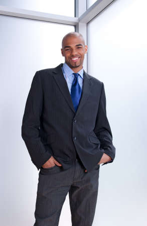 Good-looking smiling businessman standing near office window. photo