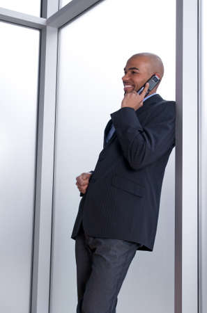 Businessman leaning against the window, talking on the phone and smiling. photo