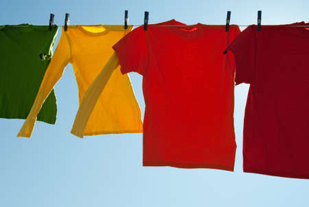 laundry line: Bright multi-colored clothes drying in the wind, on a sunny day. Stock Photo