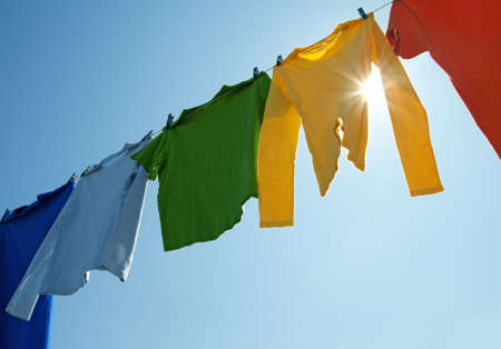 Colorful clothes hanging to dry on a laundry line and sun shining in the blue sky.