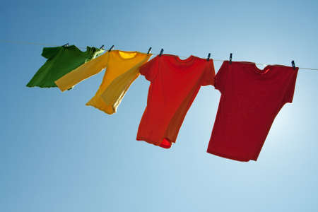 varal: Colorful clothes hanging to dry in the blue sky, on a sunny and windy day.